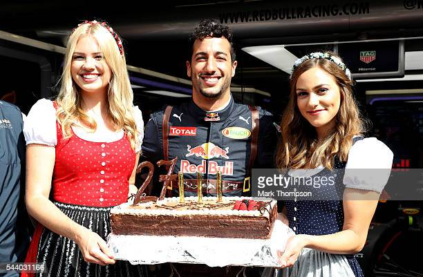 Daniel Ricciardo of Australia and Red Bull Racing celebrates his 27th birthday with a cake and a couple of girls dressed in traditional Austrian...