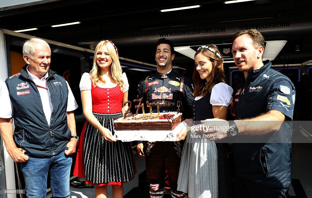 Daniel Ricciardo of Australia and Red Bull Racing celebrates his 27th birthday with a cake, Red Bull Racing Team Consultant Dr Helmut Marko, Red Bull Racing Team Principal Christian Horner and a couple of girls dressed in traditional Austrian dirndl dresses before practice for the Formula One Grand Prix of Austria at Red Bull Ring on July 1, 2016 in Spielberg, Austria.