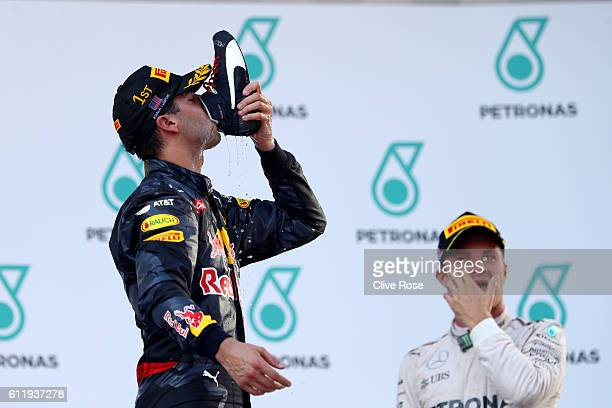 Daniel Ricciardo of Australia and Red Bull Racing celebrates his win on the podium nexr to Nico Rosberg of Germany and Mercedes GP during the...