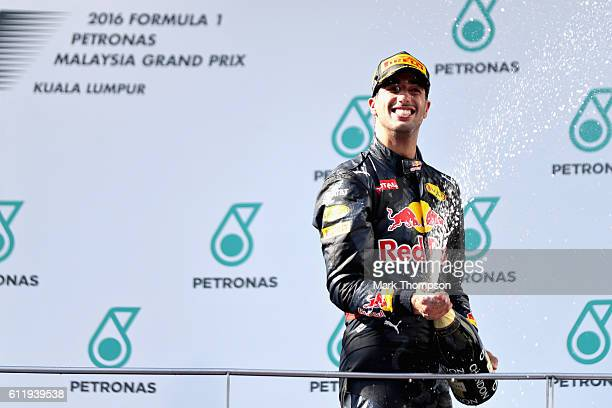 Daniel Ricciardo of Australia and Red Bull Racing celebrates his win on the podium during the Malaysia Formula One Grand Prix at Sepang Circuit on...