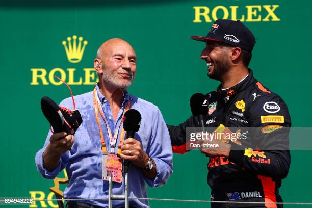 Daniel Ricciardo of Australia and Red Bull Racing celebrates on the podium with Patrick Stewart and a shoey after finishing third in the Canadian...