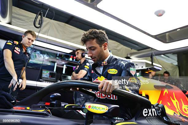 Daniel Ricciardo of Australia and Red Bull Racing climbs into his car fitted with the halo in the garage during practice for the Formula One Grand...