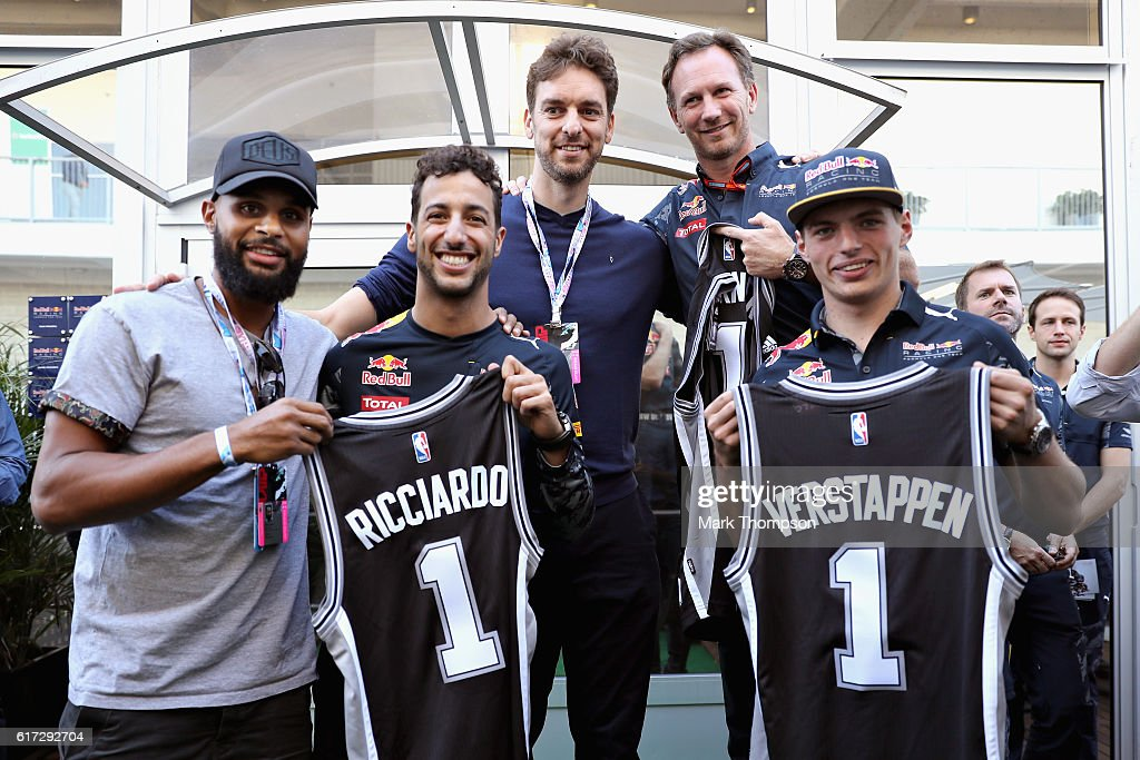Daniel Ricciardo of Australia and Red Bull Racing, Max Verstappen of Netherlands and Red Bull Racing, and Red Bull Racing Team Principal Christian Horner are given San Antonio Spurs jerseys by San Antonio Spurs basketball players Patty Mills and Pau Gasol after qualifying for the United States Formula One Grand Prix at Circuit of The Americas on October 22, 2016 in Austin, United States.