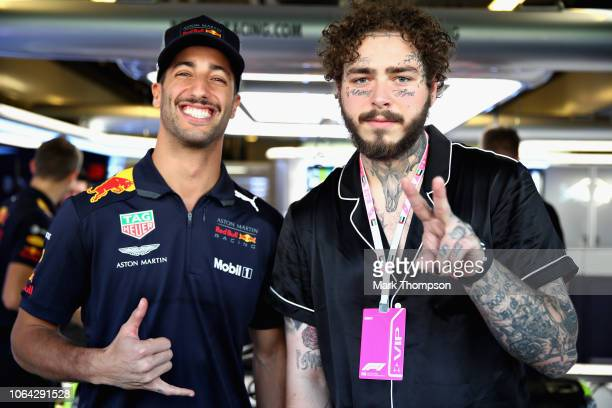 Daniel Ricciardo of Australia and Red Bull Racing poses for a photo with American rap artist Post Malone outside the Red Bull Racing garage during...