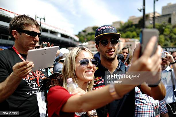 Daniel Ricciardo of Australia and Red Bull Racing poses for a photo with a fan during previews to the Monaco Formula One Grand Prix at Circuit de...