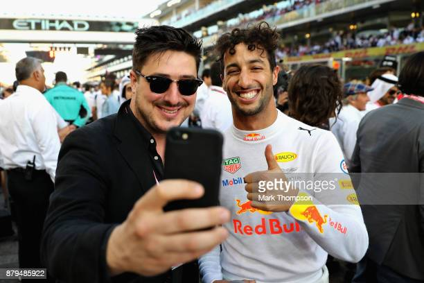 Daniel Ricciardo of Australia and Red Bull Racing poses for a photo with Marcus Mumford of Mumford and Sons on the grid before the Abu Dhabi Formula...