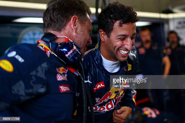 Daniel Ricciardo of Australia and Red Bull Racing shares a joke with Red Bull Racing Team Principal Christian Horner in the garage during practice...