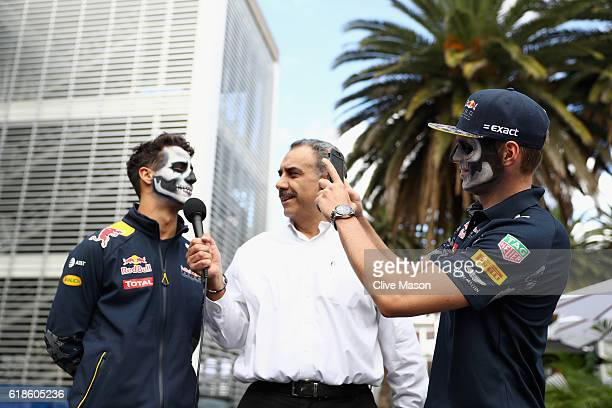 Daniel Ricciardo of Australia and Red Bull Racing talks to the media in the Paddock while Max Verstappen of Netherlands and Red Bull Racing takes a...