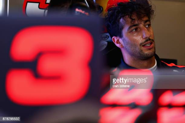 Daniel Ricciardo of Australia and Red Bull Racing talks with a Red Bull Racing team member in the garage during practice for the Abu Dhabi Formula...