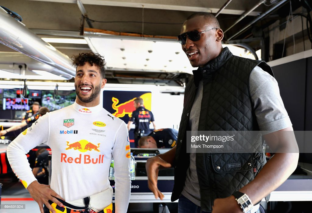 Daniel Ricciardo of Australia and Red Bull Racing talks with NBA player Bismack Biyombo of Congo in the Red Bull Racing garage during qualifying for the Canadian Formula One Grand Prix at Circuit Gilles Villeneuve on June 10, 2017 in Montreal, Canada.