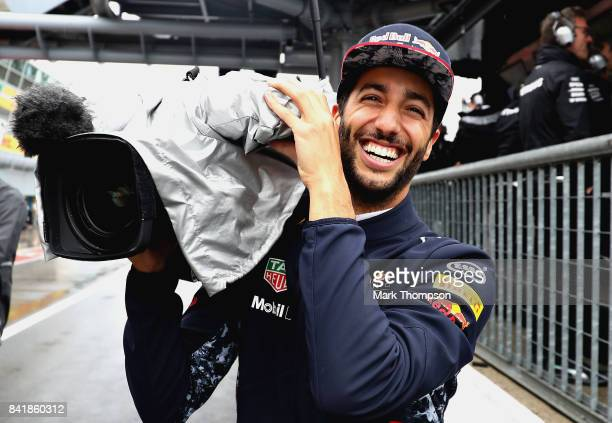 Daniel Ricciardo of Australia and Red Bull Racing uses a TV camera in the Pitlane during qualifying for the Formula One Grand Prix of Italy at...