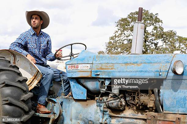 Daniel Ricciardo of Australia and Red Bull Racing works as a ranch hand for a day during previews ahead of the United States Formula One Grand Prix...