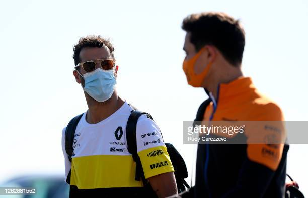 Daniel Ricciardo of Australia and Renault Sport F1 and Lando Norris of Great Britain and McLaren F1 talk as they arrive at the circuit before...