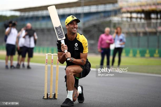 Daniel Ricciardo of Australia and Renault Sport F1 plays cricket on track during previews ahead of the F1 Grand Prix of Great Britain at Silverstone...