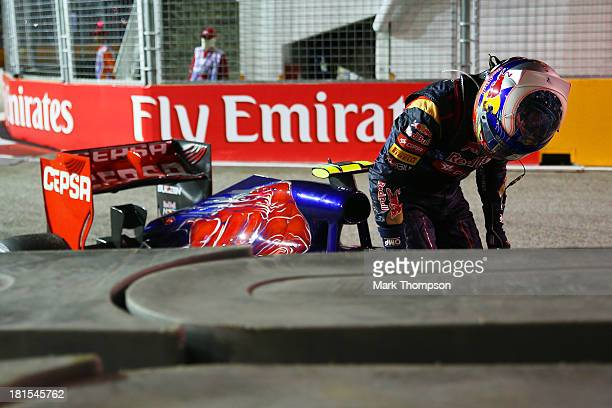 Daniel Ricciardo of Australia and Scuderia Toro Rosso climbs from hiscar after crashing into a barrier during the Singapore Formula One Grand Prix at...