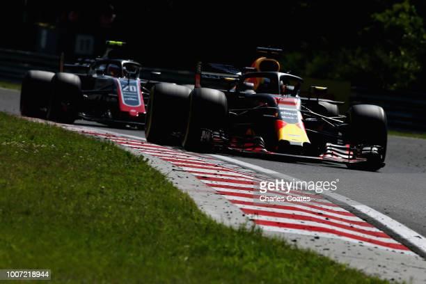 Daniel Ricciardo of Australia driving the Aston Martin Red Bull Racing RB14 TAG Heuer leads Kevin Magnussen of Denmark driving the Haas F1 Team VF18...