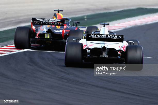 Daniel Ricciardo of Australia driving the Aston Martin Red Bull Racing RB14 TAG Heuer leads Romain Grosjean of France driving the Haas F1 Team VF18...