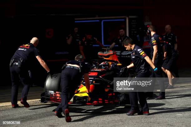 Daniel Ricciardo of Australia driving the Aston Martin Red Bull Racing RB14 TAG Heuer is pushed back into the garage by his team during day four of...
