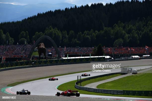 Daniel Ricciardo of Australia driving the Aston Martin Red Bull Racing RB14 TAG Heuer leads Kimi Raikkonen of Finland driving the Scuderia Ferrari...