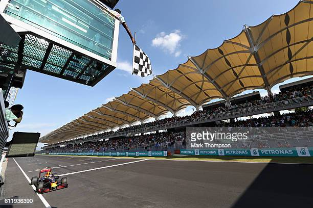 Daniel Ricciardo of Australia driving the Red Bull Racing Red BullTAG Heuer RB12 TAG Heuer crosses the line to take the chequered flag and the win...