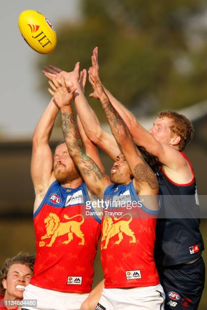 Daniel Rich and Allen Christensen of the Lions jump for the mark during the 2019 JLT Community Series AFL match between the Melbourne Demons and the...