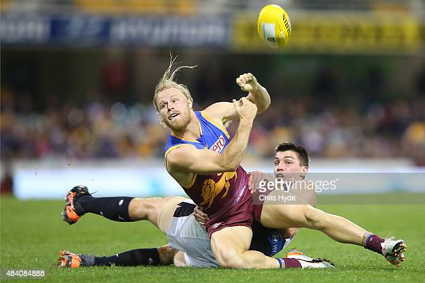 Daniel Rich of the Lions handballs while tackled by Matthew Kreuzer of the Blues during the round 20 AFL match between the Brisbane Lions and the...