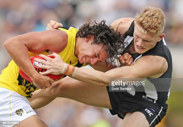 Daniel Rioli of the Tigers is tackled by Adam Treloar of the Magpies during the 2017 JLT Community Series AFL match between the Richmond Tigers and...