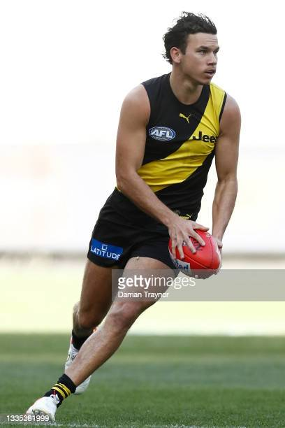 Daniel Rioli of the Tigers runs with the ball during the round 23 AFL match between Richmond Tigers and Hawthorn Hawks at Melbourne Cricket Ground on...