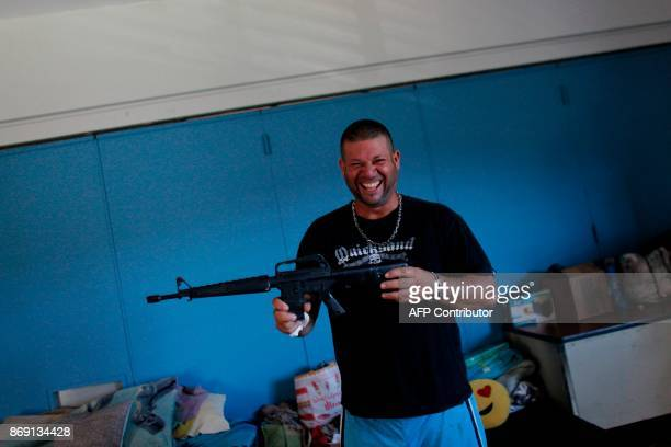 Daniel Rivera smiles as he shows a toy gun in a classroom turned bedroom in Barranquitas Puerto Rico October 31 2017 Twenty people from Barranquitas...