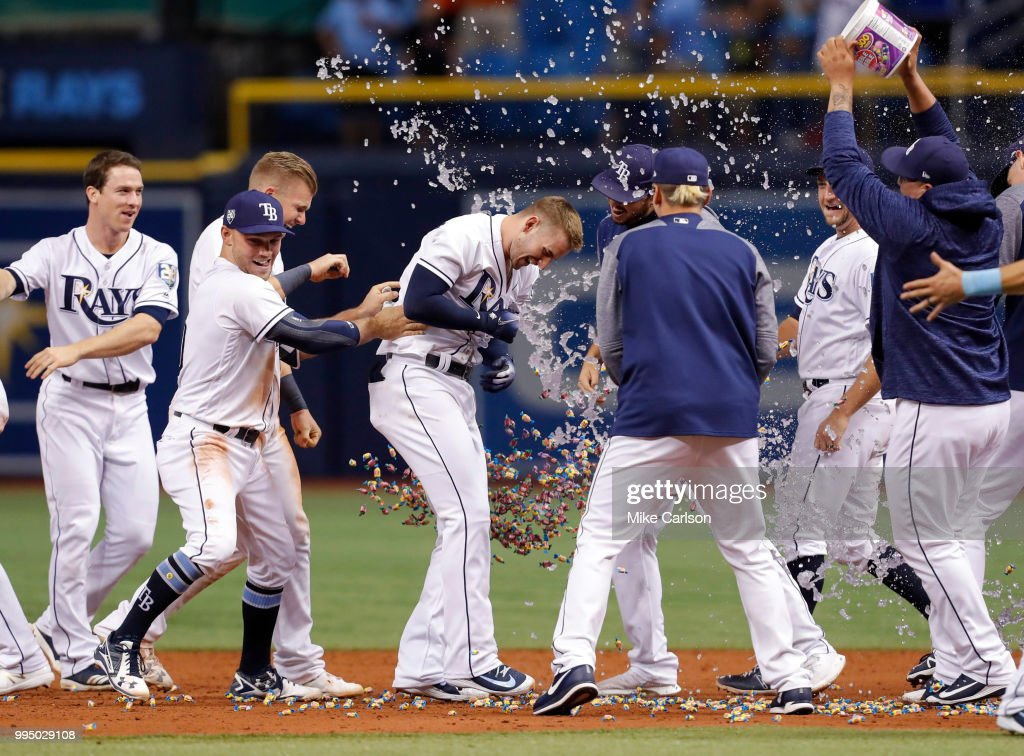 Daniel Robertson #28, center, of the Tampa Bay Rays is congratulated on his game-winning hit in the 10th inning of a baseball game at Tropicana Field on July 9, 2018 in St. Petersburg, Florida.