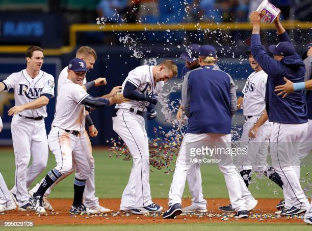 Daniel Robertson center of the Tampa Bay Rays is congratulated on his gamewinning hit in the 10th inning of a baseball game at Tropicana Field on...