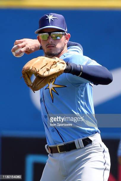 Daniel Robertson of the Rays throws the ball over to first base during the spring training game between the Tampa Bay Rays and the Toronto Blue Jays...