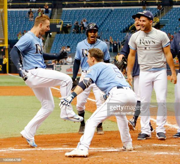 Daniel Robertson of the Tampa Bay Rays begins to celebrate with teammates at home plate after hitting a grand slam in the bottom of the ninth inning...