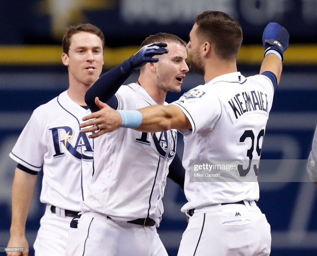 Daniel Robertson #28 of the Tampa Bay Rays, center, hugs Kevin Kiermaier #39 after hitting him in with the game-winning run in the 10th inning of a baseball game against the Detroit Tigers as Joey Wendle #18 looks on at Tropicana Field on July 9, 2018 in St. Petersburg, Florida.