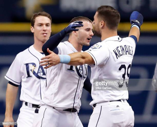 Daniel Robertson of the Tampa Bay Rays center hugs Kevin Kiermaier after hitting him in with the gamewinning run in the 10th inning of a baseball...