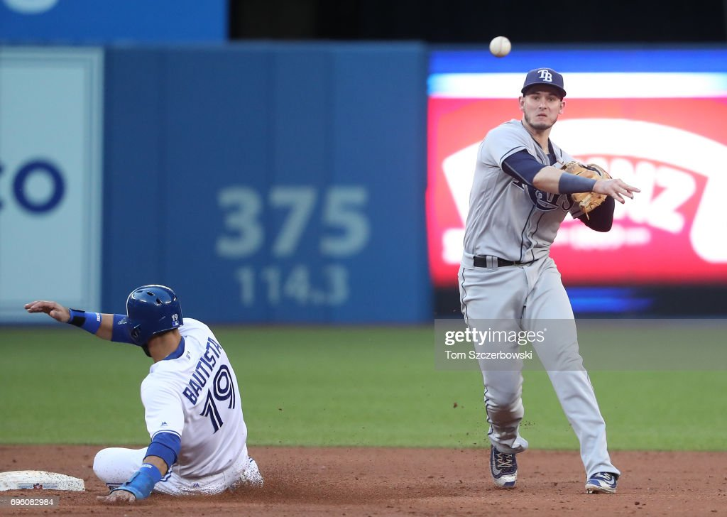 Daniel Robertson #29 of the Tampa Bay Rays gets the force out of Jose Bautista #19 of the Toronto Blue Jays at second base but cannot turn the double play as a run scores on the play in the third inning during MLB game action at Rogers Centre on June 14, 2017 in Toronto, Canada.