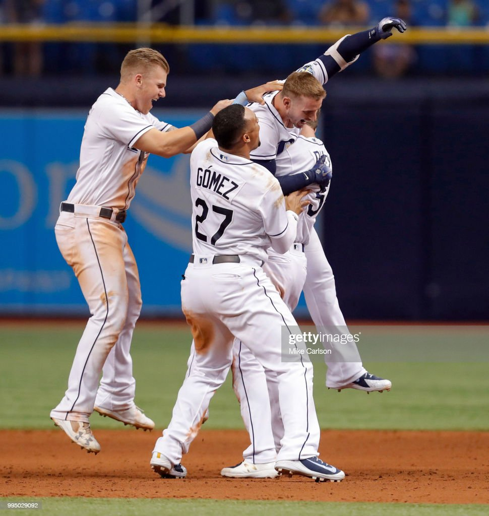 Daniel Robertson #28 of the Tampa Bay Rays is congratulated on his game-winning hit by Jake Bauers #9 and Carlos Gomez #27 in the 10th inning of a baseball game against the Detroit Tigers at Tropicana Field on July 9, 2018 in St. Petersburg, Florida.