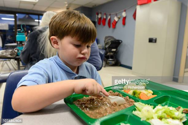Daniel Rojas eats dinner with his mother Kayle Rojas not shown at the Samaritan House on December 17 2018 in Denver Colorado Through a series of...
