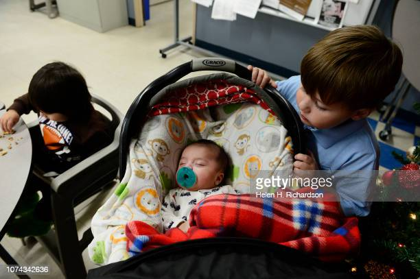 Daniel Rojas right checks on his tiny 2 month old brother Jesus middle as his other brother Omar left eats dinner at the Samaritan House on December...