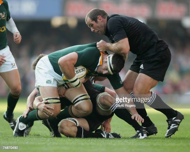 Daniel Rossouw of South Africa is tackled by Richie McCaw and Anton Oliver during the 2007 TriNations match between South Africa and New Zealand at...