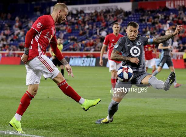 Daniel Royer of New York Red Bulls takes a shot as Francisco Calvo of Minnesota United defends at Red Bull Arena on April 06, 2019 in Harrison, New...