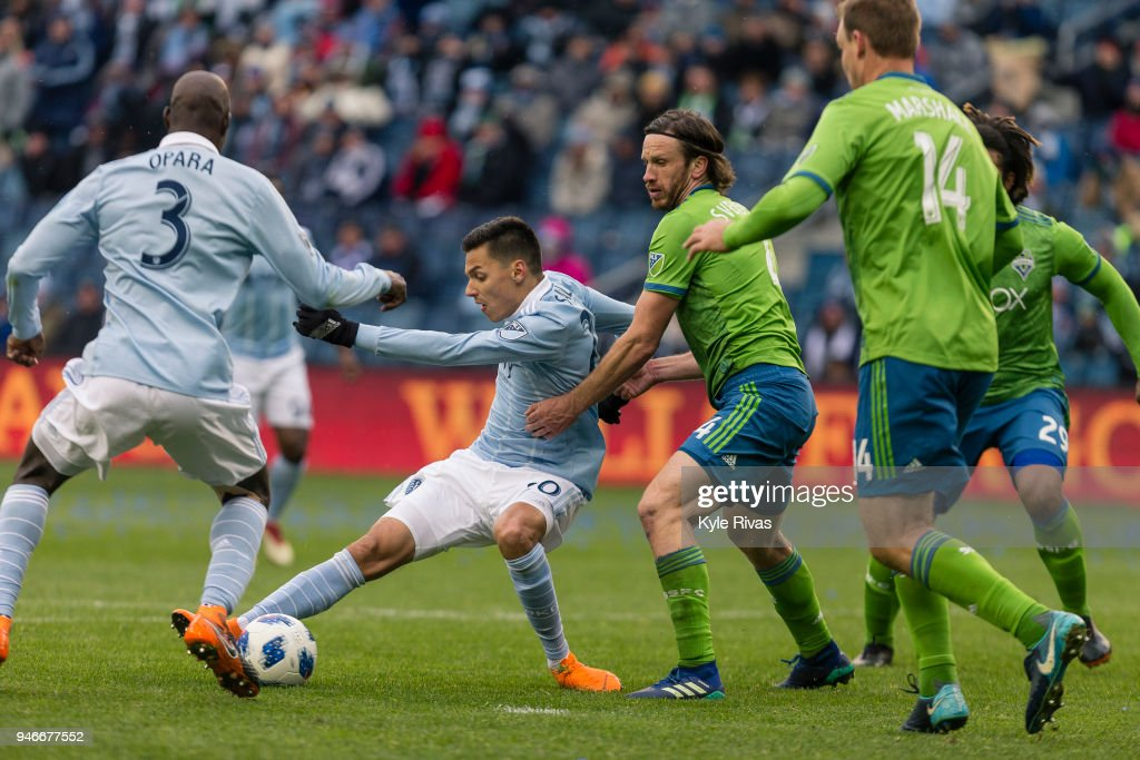 Daniel Salloi #20 of Sporting Kansas City attempt to work around Gustav Svensson #4 of Seattle Sounders during the second half on April 15, 2018 at Children's Mercy Park in Kansas City, Kansas.