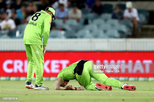 Daniel Sams of the Thunder lays on the ground after falling hard from fielding during the Big Bash League match between the Sydney Thunder and the...