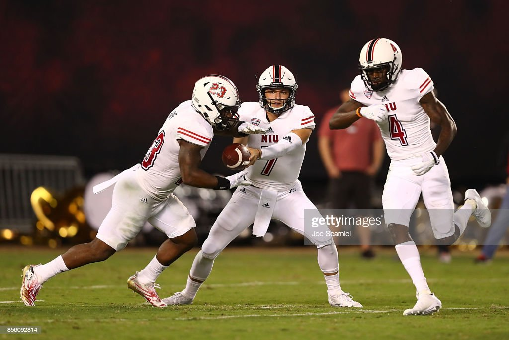 Daniel Santacaterina #7 of the Northern Illinois Huskies hands the ball off to Jordan Huff #23 as Christian Blake #4 runs by in the second quarter during the Northern Illinois v San Diego State game at Qualcomm Stadium on September 30, 2017 in San Diego, California.