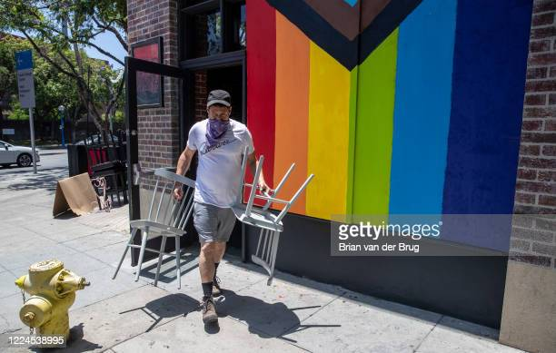 Daniel Santiago carries chairs out of the Revolver video bar, undergoing renovations on Santa Monica Blvd. On Thursday, July 2, 2020 in West...