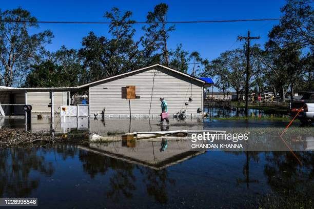 Daniel Schexnayder walks in flooded water outside his house after Hurricane Delta passed through the area on October 10, 2020 near Lake Charles,...