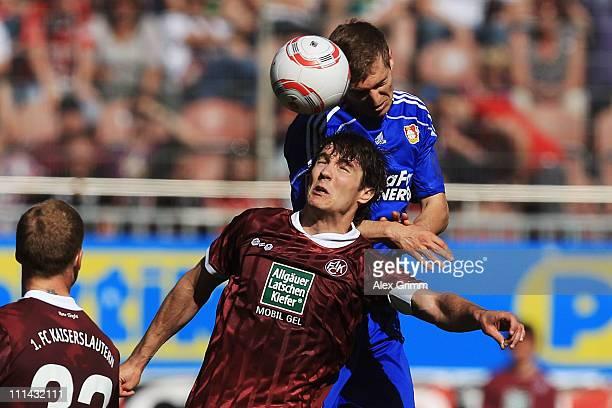 Daniel Schwaab of Leverkusen outjumps Srdjan Lakic of Kaiserslautern during the Bundesliga match between 1. FC Kaiserslautern and Bayer Leverkusen at...