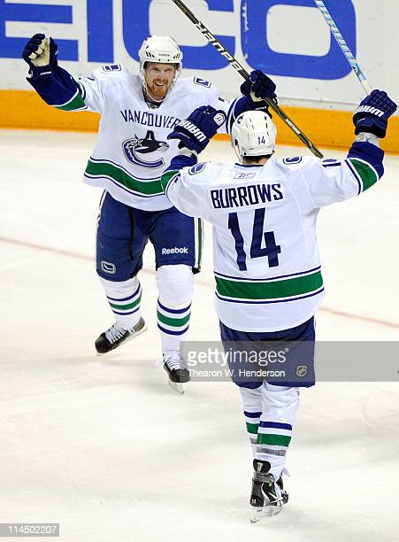 Daniel Sedin and Alex Burrows of the Vancouver Canucks celebrate teammate Sami Salo's first of two second period goals in Game Four of the Western...