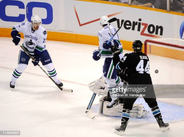 Daniel Sedin and Alex Burrows of the Vancouver Canucks watch as the puck enters the net on a shot by teammate Sami Salo for his first of two second...