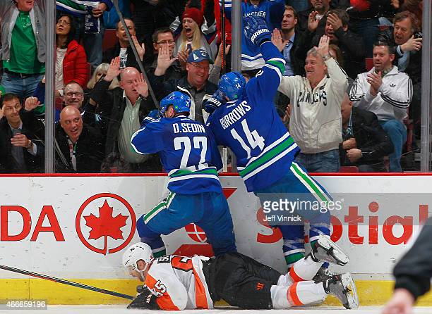 Daniel Sedin and Alexandre Burrows of the Vancouver Canucks celebrate a goal behind Nick Schultz of the Philadelphia Flyers during their NHL game at...